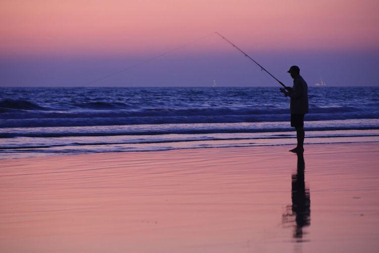 Silhouette man fishing on beach against sunset sky