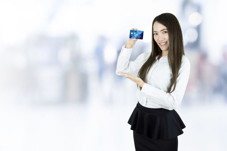 Asian business woman showing credit card on blurred background. Young Adult Women Long Hair One Person Adult Young Women Holding Beautiful Woman Standing Credit Card Asian  Female Shopping Bank Banking Present Thailand Chinese Japanese  Korean Attractive Beautiful Business Businesswoman Close-up Buying Casual Caucasian Copy Space Credit Debit Card Happy Greeting Show Lady Office Online  Paying Payment Portrait Purchase Sales Smile Young White Pretty Cute