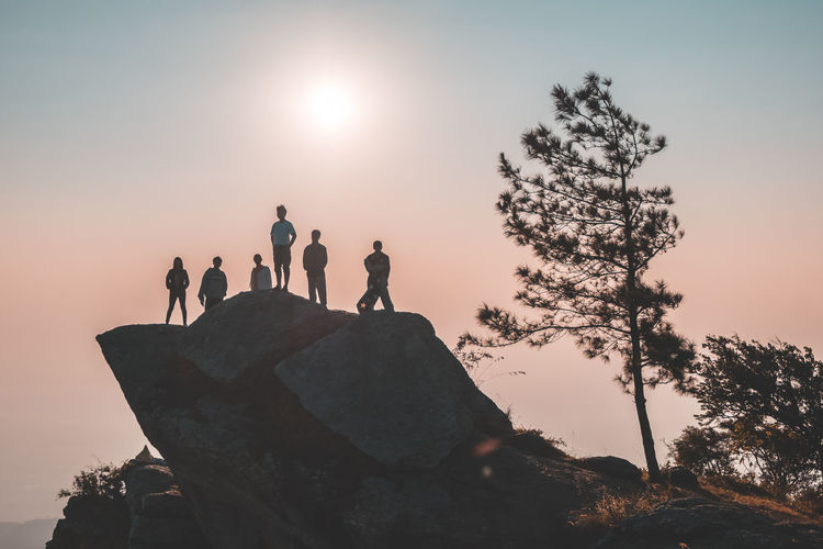 Low angle view of friends standing on rock formation against clear sky during sunset