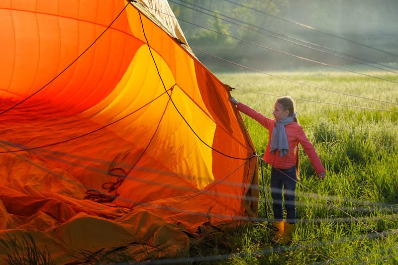 Full length of girl preparing tent on field at campsite