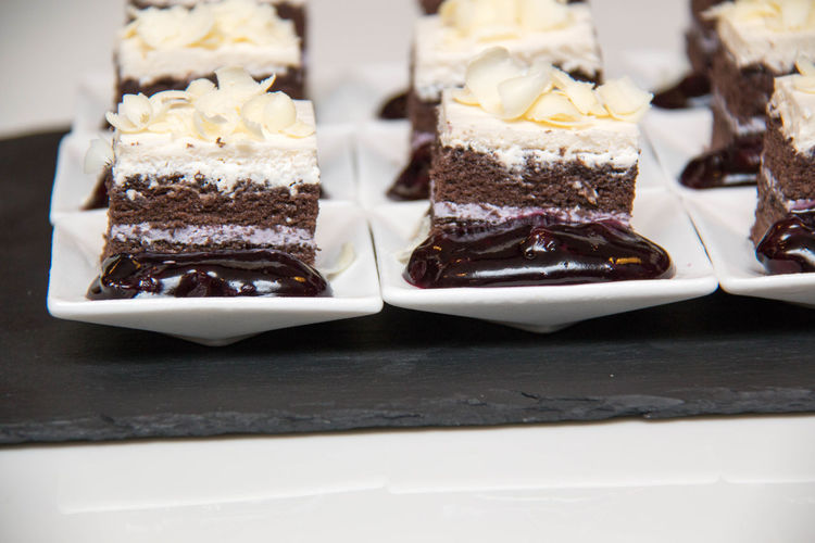 Desserts in plates on slate on table