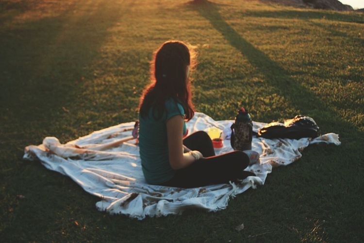 Side view of woman sitting on picnic blanket at park
