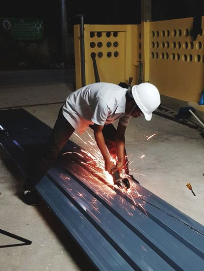 Crouching Industry Business Finance And Industry Only Men Indoors  One Person Adults Only Adult Men Skill  Working Protective Workwear One Man Only Occupation Manual Worker Headwear People Factory Full Length Day