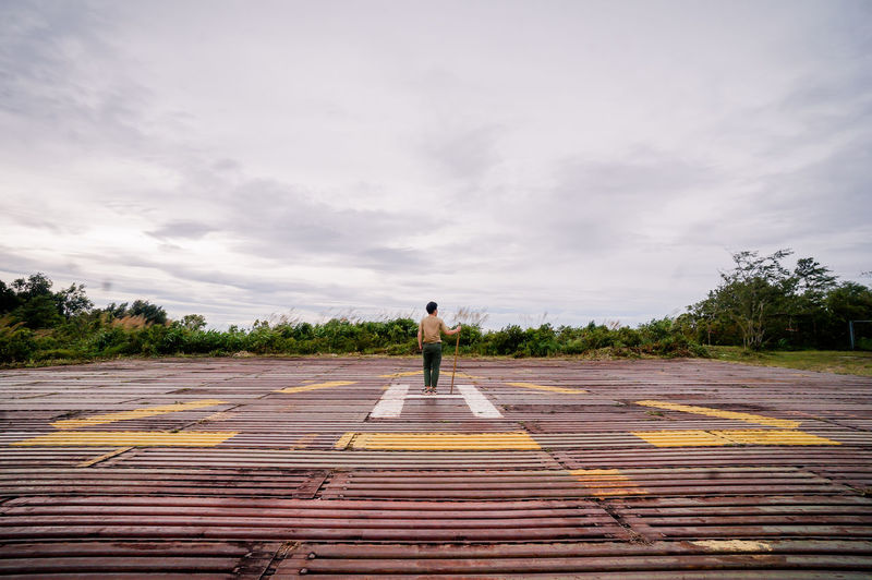 Rear view of man standing with stick on road against sky