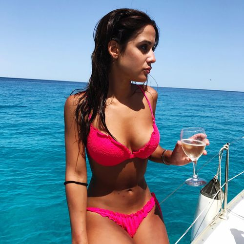 Beautiful young woman holding drink on boat in sea against sky