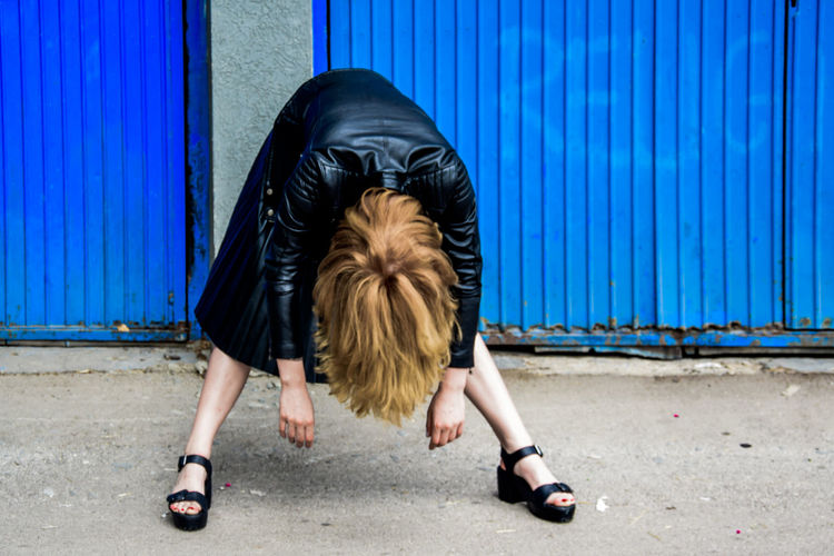 Woman Bending Over Against Blue Corrugated Iron Wall