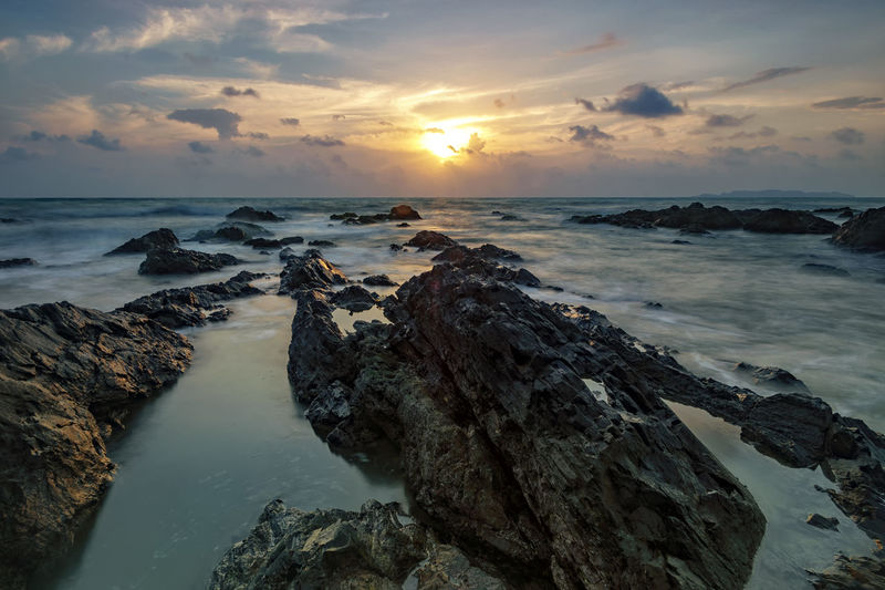 High angle view of rock formations in sea against cloudy sky at sunset