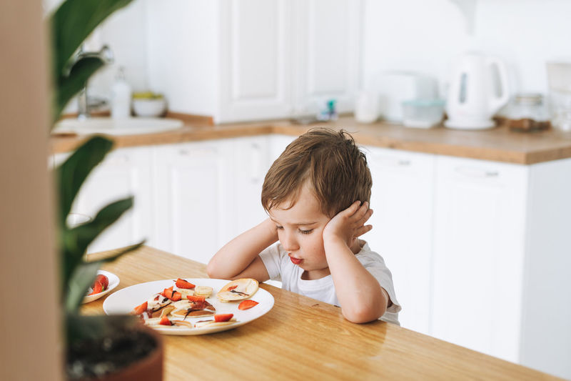Cute toddler boy sitting with puncakes with berries in kitchen home. child doesn't want to eat
