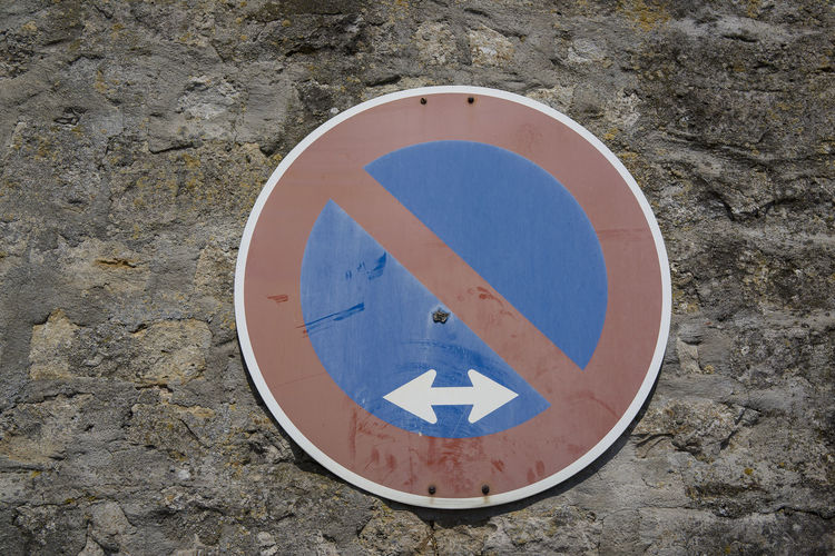 Close-up of road sign on stone wall