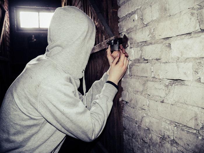 Hooded Burglar Opening Padlock In Basement