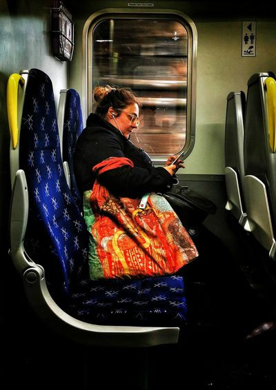 Midsection of woman sitting in train