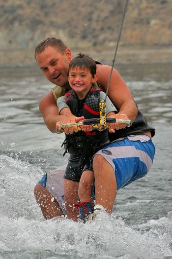 Father and son wakeboarding on sea