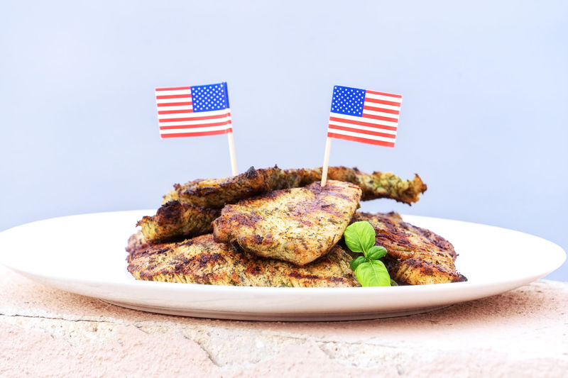 Plate with turkey steaks cooked on grill with American flags on blue background, closeup view. Independence Day of America Celebration July 4th. United States traditional dish United National Symbol July 4th Event Stars Liberty Day Flag USA Happy Greeting American Independence America Meat Party Meal Invitation Hot Emblem  BBQ Lunch Celebration Patriotic Blue Red Card Holiday Summer Barbecue Food Anniversary Picnic Grill Celebrate Steak Pork Turkey Traditional Grilled Gourmet Cooking Barbeque Outdoor Grilling Appetizer Homemade Snack