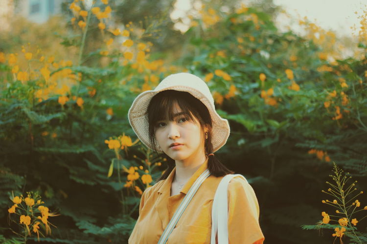 Portrait of beautiful young woman standing against plants