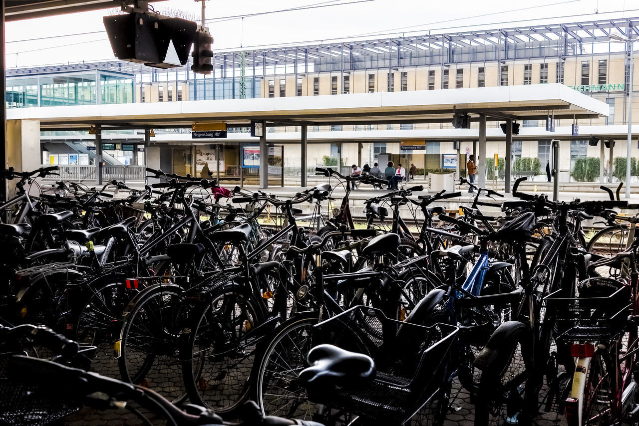 transportation, bicycle, land vehicle, mode of transportation, built structure, architecture, stationary, parking lot, day, no people, bridge, travel, bridge - man made structure, building exterior, connection, city, outdoors, rail transportation, bicycle rack, parking