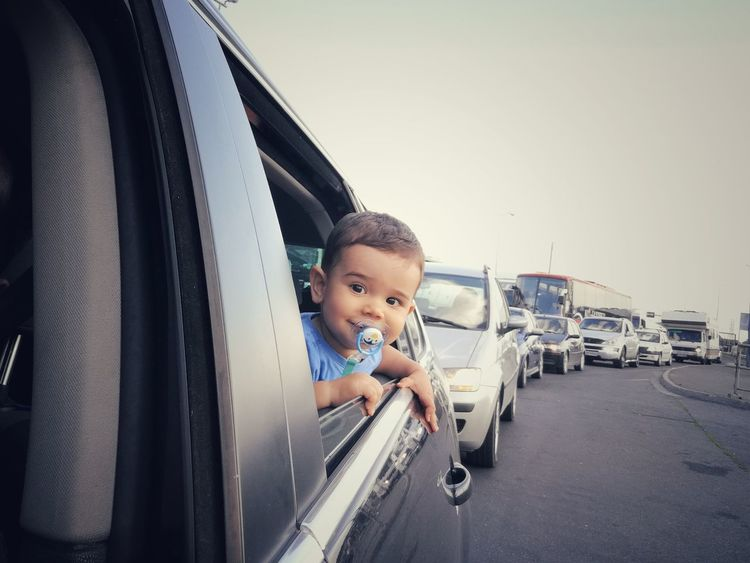 Baby boy in car on a road trip Child Boy Childhood Car Window Open Window Baby In Car Child In Car On Window Looking Through Window Baby Boy Pacifier In Mouth Road Trip Happy Enthusiasm Smiling Enjoying Life Enjoying Trip Happy Baby Traffic Jam Happy Moments Transportation Street Vehicle