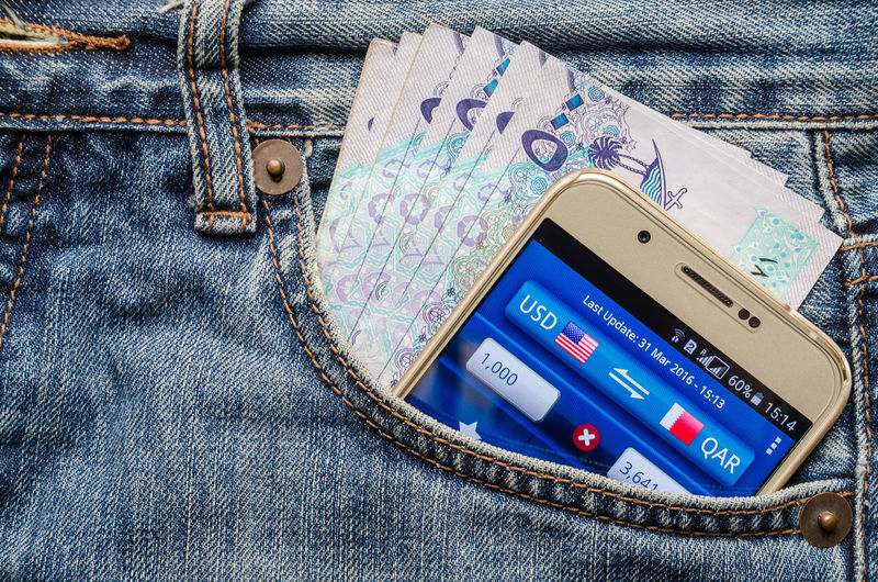 Currency Blue Casual Clothing Close-up Communication Connection Denim Domestic Animals Fashion Finance Indoors  Jeans Mobile Phone No People Pattern Personal Accessory Pocket  Portable Information Device Qatar Riyal Smart Phone Still Life Technology Textile Wireless Technology