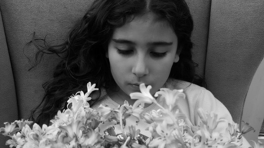 Girl Holding Flowers While Sitting On Sofa