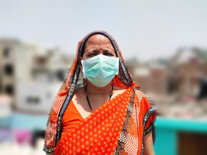 Portrait of mature woman wearing mask standing standing outdoors