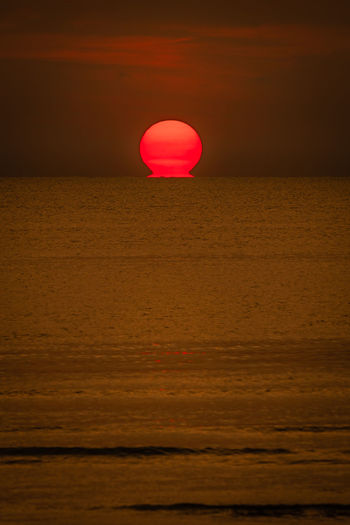 Red balloon on sea against sky during sunset