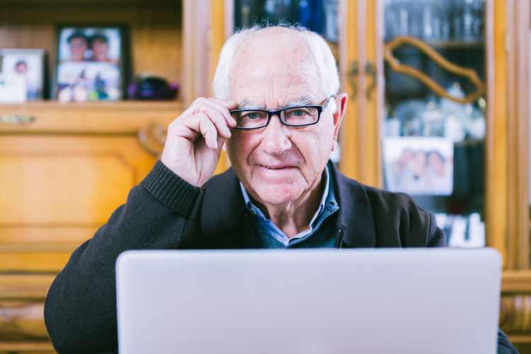 Senior man using laptop to surfing the net. Communication Computer Connection Day Eyeglasses  Front View Home Interior Indoors  Internet Laptop Lifestyles Men One Person One Senior Man Only People Real People Retirement Senior Senior Adult Senior Men Sitting Surfing The Net Technology Using Laptop Wireless Technology