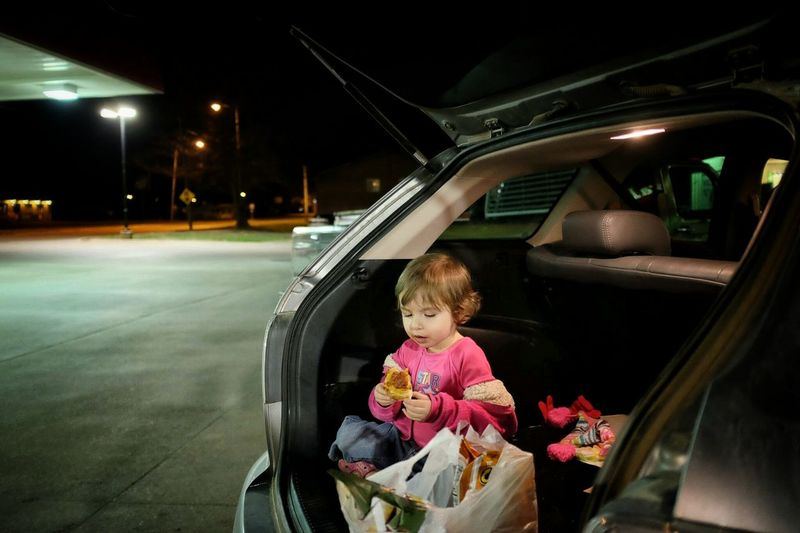Girl eating food while sitting in car trunk