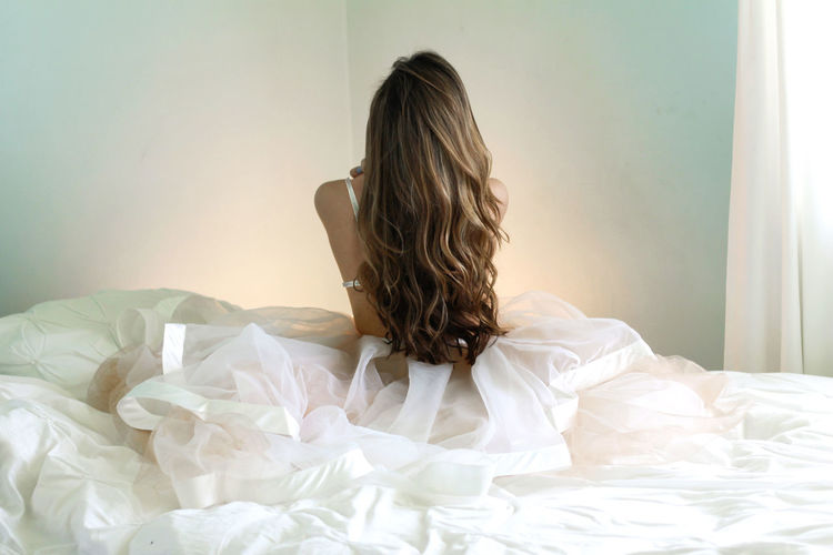 Rear View Of Woman With Long Hair Sitting On Bed