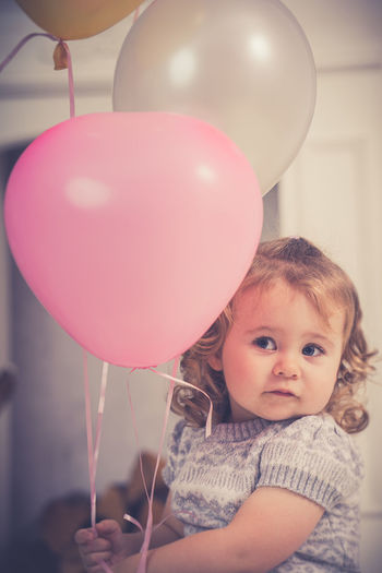 Portrait of cute boy with balloons at home