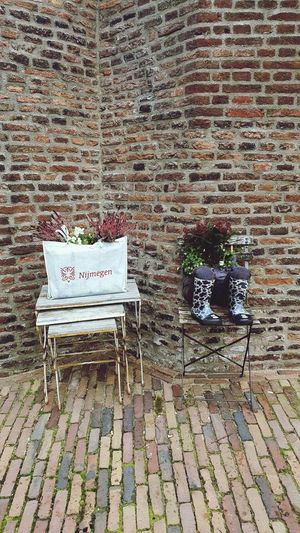 Empty chairs against brick wall