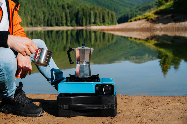 Man preparing coffee on camping stove by the lake