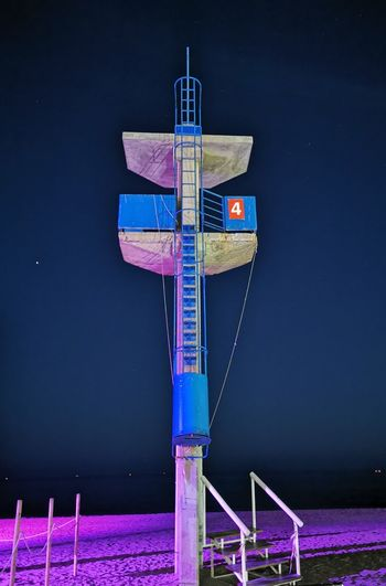 Low angle view of illuminated communications tower against clear blue sky