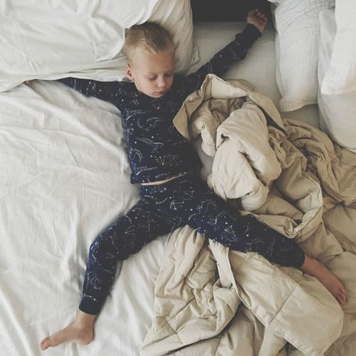 Full Length Of Boy Sleeping On Bed At Home