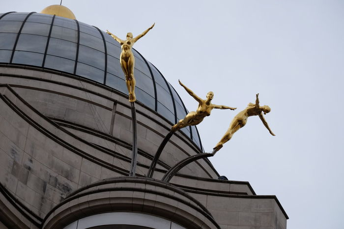 Sculpture, Piccadilly Circus Composition Flying High Fun GB London Unusual Acrobats Architectural Feature Art Deco Style Building Exterior Capital City Clear Sky Dome Gold Coloured Grey Sky Human Representation Low Angle View No People Outdoor Photography Sculpture Statue Travel Destination Uk Unusual Beauty Unusual Perspective