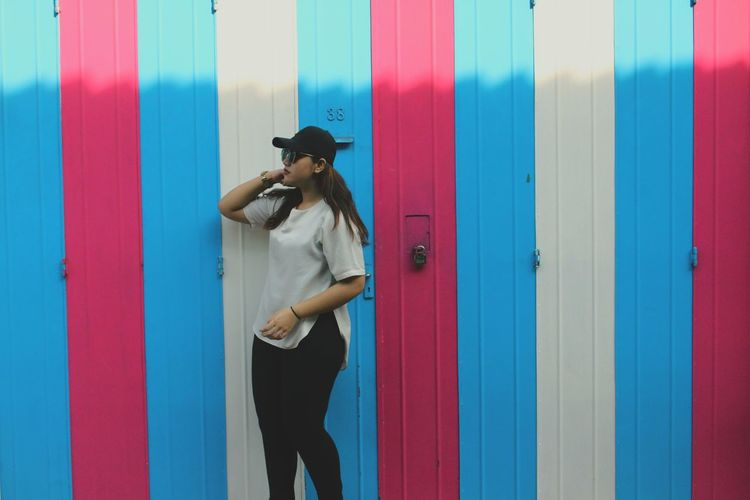 Woman in hat standing against colorful wall on sunny day