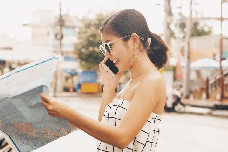 Side view of smiling mid adult woman with world map using phone on street