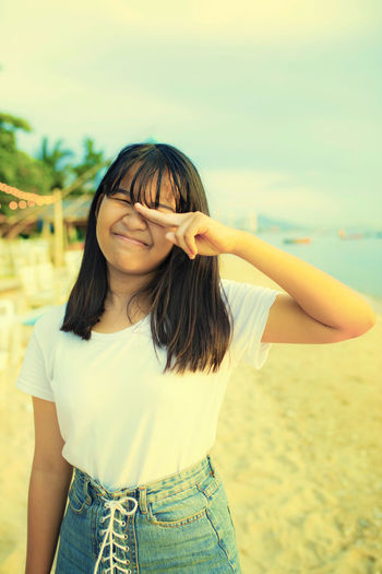 Girl with eyes closed standing at beach