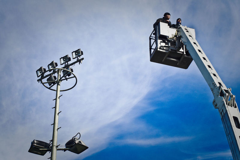 Low angle view of construction workers on cherry picker