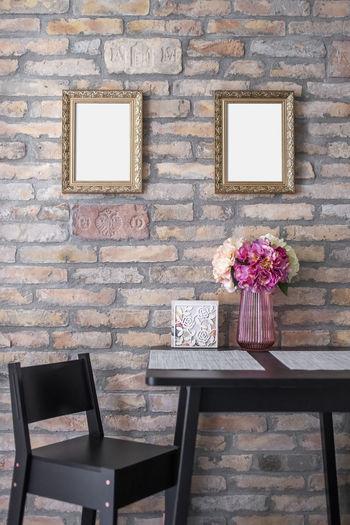 Flower vase on table against wall