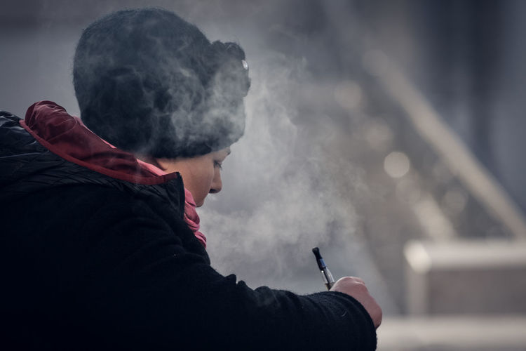 Woman Addiction Bad Habit Cigar Cigarette  Close-up Danger Focus On Foreground Holding Leisure Activity Lifestyles Night One Person Outdoors People Real People RISK Sad Side View Sky Smoke - Physical Structure Smoking - Activity Smoking Issues Social Issues Young Adult