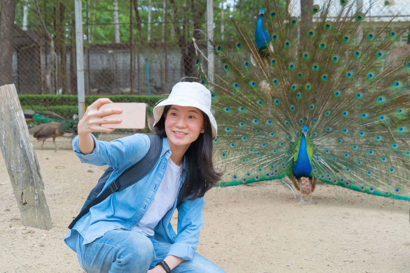 Smiling woman doing selfie with peacock