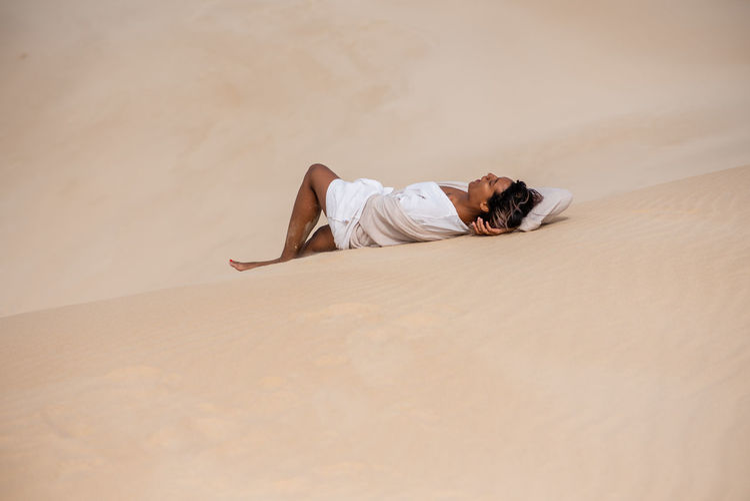 Portrait of man resting on sand