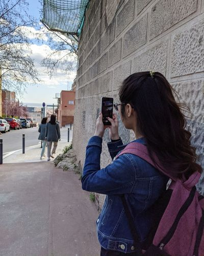 Young woman photographing through smart phone in city