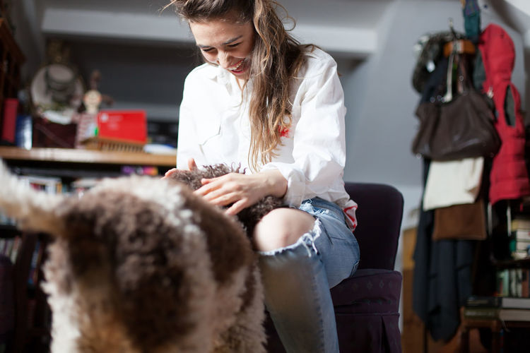 dog welcomes young woman after returning home Happiness Happy Home Stylish Animal Attractive Casual Clothing Cheerful Companion Cuddling Cute Dog Domestic Girl Indoors  Joy Looking Down Pet Sitting Smiling Togetherness Trendy Welcome Women Young Adult