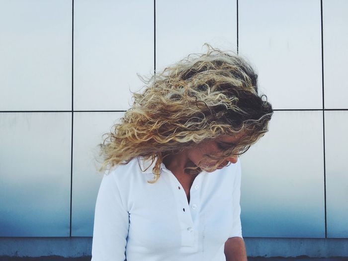 Woman with windswept curly blond hair standing against wall