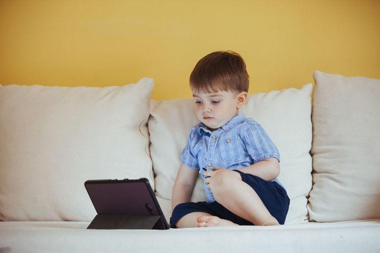 Boy looking at camera while sitting on sofa at home