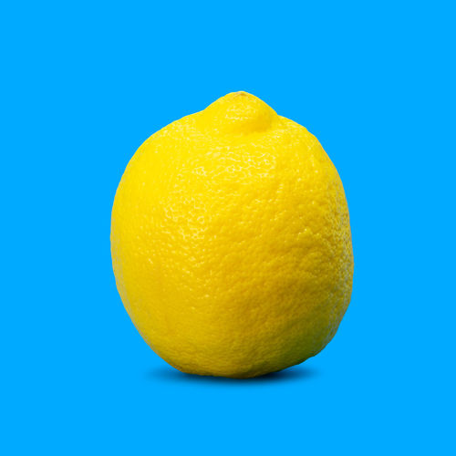 Close-up of lemon against blue background