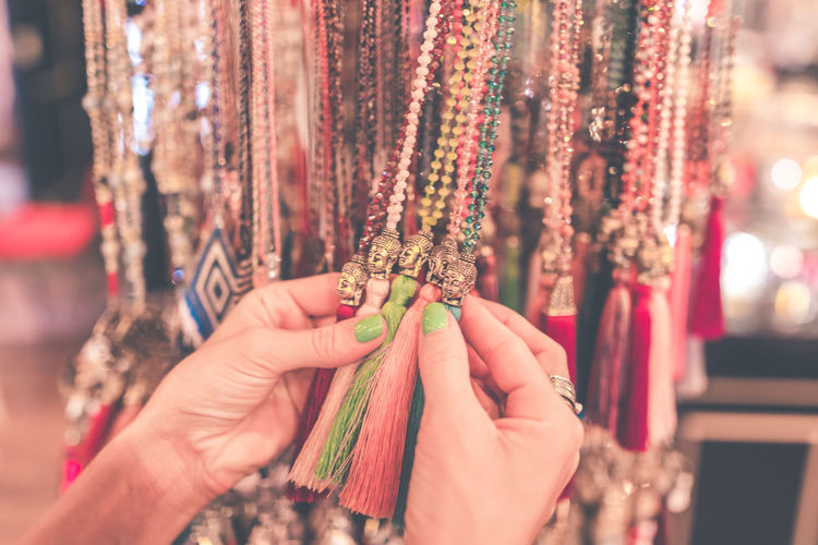 Cropped hands of woman holding jewelry hanging at market