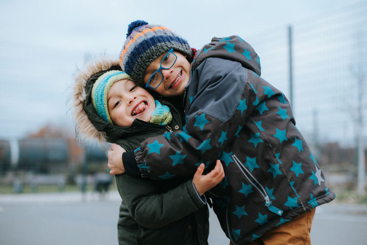 Hug between two young boys during winter