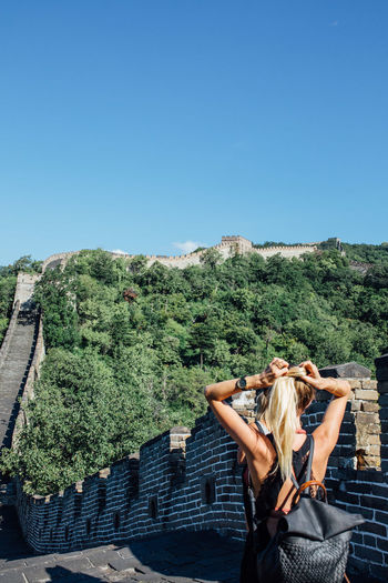 Rear view of woman tying hair while standing at great wall of china