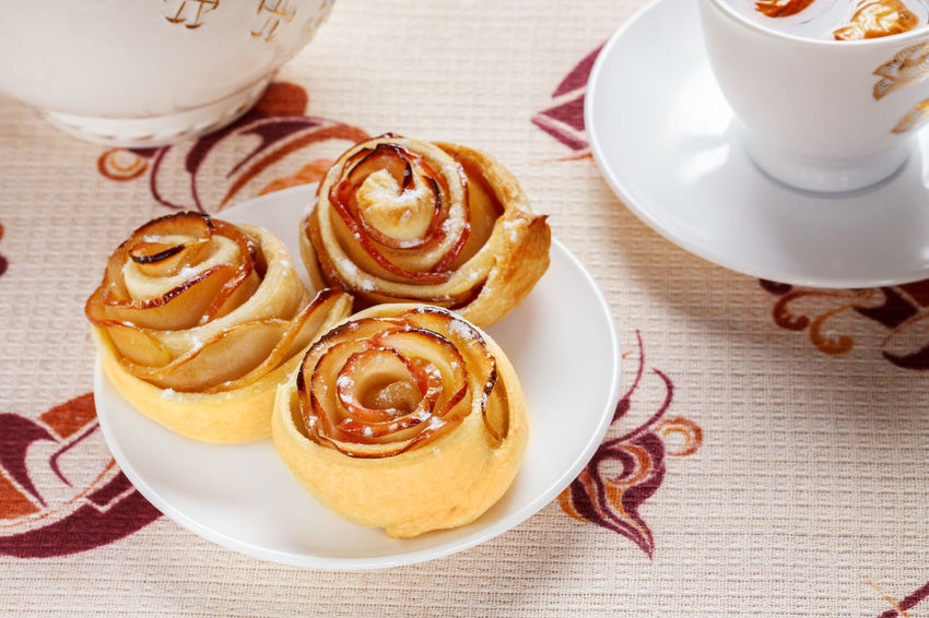 Three ruddy buns on a white saucer with herbal apple tea in a cup and a teapot in the background. Appetising Apple Slices Breakfast Buns Close-up Day Dessert Drink Food Food And Drink Freshness High Angle View Indoors  Napkin No People Plate Ready-to-eat Rosettes Saucer Sweet Food Table Tablecloth Teapot Three